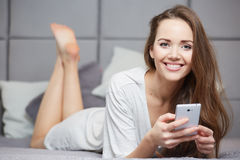 Woman reading a text message in her bright bedroom Royalty Free Stock Images