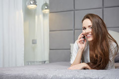Woman reading a text message in her bright bedroom Royalty Free Stock Photo