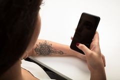 Woman reading a text message on her mobile. Phone in a close up over the shoulder view of the blank screen in her hand Royalty Free Stock Photography