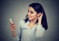 Woman reading text message on smart phone having a pleasant conversation stock photo