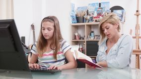 Woman reading a text to a teenage girl as she types it on the computer. Improving typing skills. Parent helping her kid stock footage
