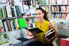 Woman reading textbook in shop Stock Photo