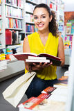Woman reading textbook in shop Royalty Free Stock Image