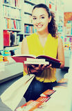 Woman reading textbook in shop. Portrait of glad young woman looking interested and reading textbook in book shop Stock Photos