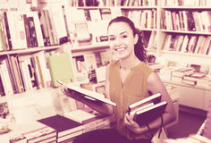 Woman reading textbook in shop. Portrait of glad young woman looking interested and reading textbook in book store Royalty Free Stock Photos