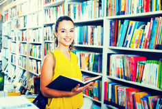 Woman reading textbook in shop. Portrait of happy young woman looking interested and reading textbook in book shop Stock Photos