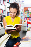 Woman reading textbook in shop. Portrait of positive young woman looking interested and reading textbook in book shop Royalty Free Stock Image