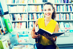 Woman reading textbook in shop Stock Images