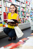 Woman reading textbook in shop. Portrait of smiling young woman looking interested and reading textbook in book store Royalty Free Stock Image