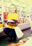 Woman reading textbook in shop. Portrait of smiling young woman looking interested and reading textbook in book store Stock Photos