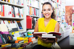 Woman reading textbook in shop. Portrait of smiling young woman looking interested and reading textbook for school in book shop Stock Photography
