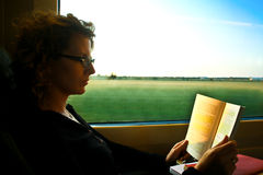 Woman reading in the train. Woman reading a book in the train royalty free stock images