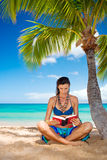 Woman reading on tropical beach Stock Photos