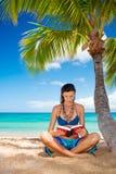Woman reading on tropical beach. Tropical woman reading on beach under palm tree Stock Photos