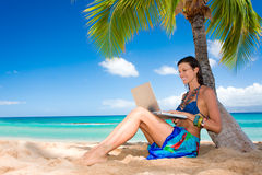 Woman reading on tropical beach. Tropical woman on hawaii beach with blue water with laptop Stock Image