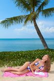 Woman reading on a tropical beach. Beautiful blonde woman relaxing on a pink towel under a palm tree reading on a tropical beach with ocean backdrop stock photography