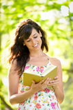 Woman reading and walking on park Stock Image