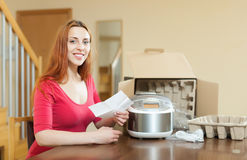 Woman  reading  warranty card for new slow cooker Stock Photography
