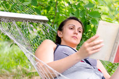 Woman reading whilst relaxing in a hammock Royalty Free Stock Images
