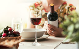 Woman reading a wine label. Woman having lunch at the restaurant and reading a wine label on the bottle, fine drinking and wine culture concept Stock Images