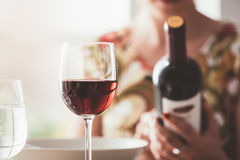 Woman reading a wine label. Woman having lunch at the restaurant and reading a wine label on the bottle, fine drinking and wine culture concept Royalty Free Stock Images