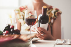 Woman reading a wine label. Woman having lunch at the restaurant and reading a wine label on the bottle, fine drinking and wine culture concept Stock Image