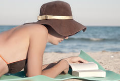 Woman reads book on the beach Royalty Free Stock Image