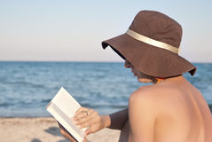 Woman reads book on the beach Stock Photo