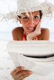 Woman reads a book on beach Stock Photo
