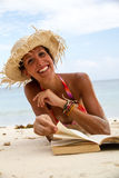 Woman reads a book on beach Stock Photography