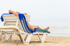 Woman reads book at beach royalty free stock image