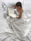 Woman reads a book in bed Royalty Free Stock Image
