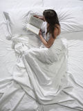 Woman reads a book in bed Stock Images