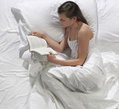 Woman reads a book in bed Stock Image