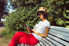 Woman reads a book on a bench Stock Image