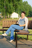 Woman reads a book on a bench in the park Stock Photos
