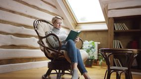 Woman reads a book in a chair. On attic stock video footage