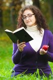 Woman reads book on green grass Stock Photography