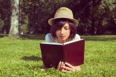 Woman reads a book on the meadow Stock Photography