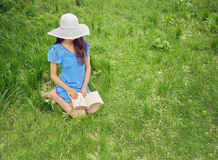 Woman reads a book on nature Royalty Free Stock Photo