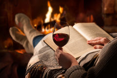 Woman reads book near fireplace Royalty Free Stock Images