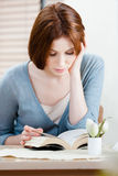 Woman reads the book at the shop Stock Photography