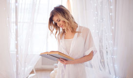 Woman reads a book sitting on bed. Young beautiful girl in her bedroom Royalty Free Stock Photo