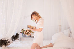 Woman reads a book sitting on bed. Young beautiful girl in her bedroom. Glamour portrait of beautiful woman model with fresh daily makeup and romantic wavy royalty free stock photo