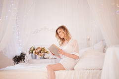 Woman reads a book sitting on bed. Young beautiful girl in her bedroom Stock Images