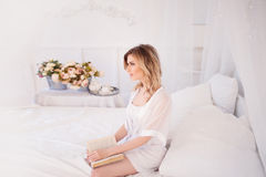 Woman reads a book sitting on bed. Young beautiful girl in her bedroom. Glamour portrait of beautiful woman model with fresh daily makeup and romantic wavy royalty free stock images