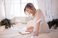 Woman reads a book sitting on bed. Young beautiful. Glamour portrait of beautiful woman model with fresh daily makeup and romantic wavy hairstyle. Fashion shiny stock image