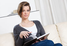 Woman reads the book sitting on the sofa Stock Image
