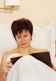 Woman reads a book before sleeping Stock Photography