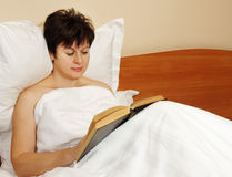 Woman reads a book before sleeping Royalty Free Stock Photos